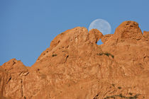 A full moon sets behind the Kissing Camels sandstone formation by Danita Delimont