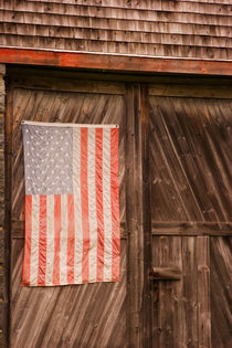 Faded American flag on door of old barn by Danita Delimont