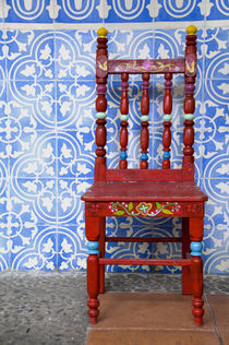 Typical blue tile walls with red chair von Danita Delimont