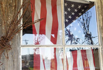 Flag in window next to coil of barbed wire von Danita Delimont