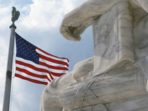A flag and statue in front of the United States Supreme Court building by Danita Delimont