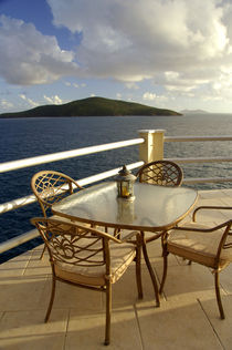 View of the Atlantic and the island of Big Hans Lollik from villa deck with table and chairs by Danita Delimont