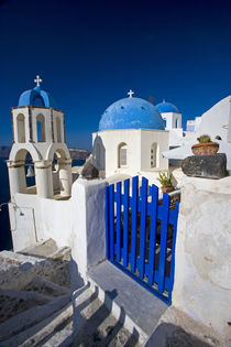 Greece and Greek Island of Santorini town of Oia with Blue Domed Churches with white and colorful buidling surrounding them von Danita Delimont