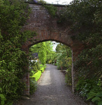 The Dromoland Castle very green walled garden path through a brick archway von Danita Delimont