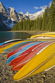 Moraine Lake and rental canoes stacked on shore by Danita Delimont