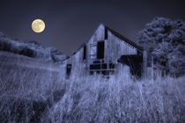 Digitally altered infrared photograph of an old weathered barn in a rural area with a full moon overhead by Danita Delimont