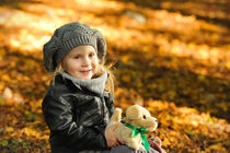 Little girl in autumn leaves by Waldek Dabrowski