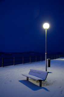 Park bench covered in snow at night by kbhsphoto