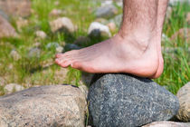 Bare feet of young man balancing on a stone von kbhsphoto