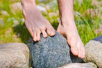 Bare feet of young man balancing on a stone by kbhsphoto