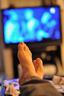 Man watching television feet up by Sami Sarkis Photography