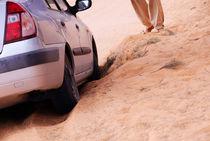 Man standing by car stuck in sand in desert von Sami Sarkis Photography
