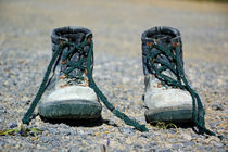 Pair of used work boots on road von Sami Sarkis Photography
