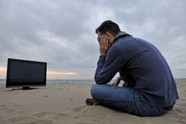 Man with TV on beach at sunset by Sami Sarkis Photography