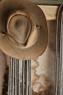 Old leather hat and ropes hanging at stable by Sami Sarkis Photography