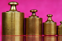 Copper weights on pink background von Sami Sarkis Photography