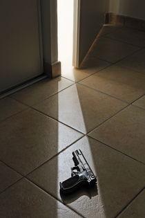 Light rays on Handgun from doorway left ajar von Sami Sarkis Photography