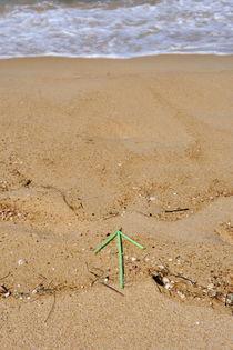 Plastic arrow on beach by water's edge by Sami Sarkis Photography