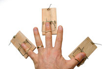 Man's hand with three mousetraps on fingers von Sami Sarkis Photography