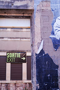 Wall with exit signs in French and English von Sami Sarkis Photography