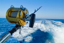 Rod and reel on board of game fishing boat by Sami Sarkis Photography