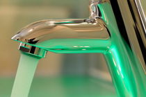 Chrome sink tap with running water by Sami Sarkis Photography