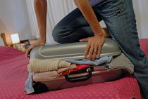 Woman trying to close overflowed suitcase on bed von Sami Sarkis Photography