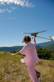 Girl (6-7) flying model plane in field by Sami Sarkis Photography