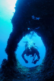 Diver swimming through hole by Sami Sarkis Photography