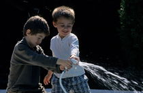 Two boys (11-13) playing with garden hose by Sami Sarkis Photography