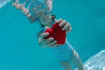 Girl (6-7) holding heart shaped symbol in swimming pool by Sami Sarkis Photography