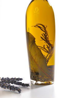 Bottle of herb-infused olive oil and lavender by Sami Sarkis Photography