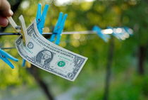 Man's hand taking one US dollars banknote hanging on clothesline von Sami Sarkis Photography