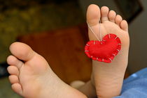 Valentine heart hanging on girl's (6-7) barefeet by Sami Sarkis Photography