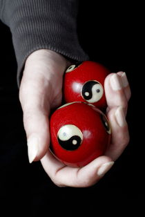 Woman holding Yin Yang balls in hand by Sami Sarkis Photography