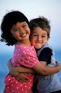 Girl and boy (7-9) embracing by Sami Sarkis Photography