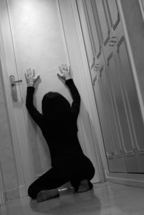 Woman kneeling in corridor with hands on closed door von Sami Sarkis Photography