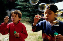 Girl and boy blowing bubble-wands von Sami Sarkis Photography