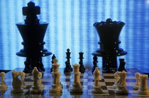 Chess board with King and Queen chess pieces in front of TV screen by Sami Sarkis Photography