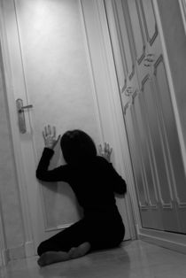 Woman sitting in corridor with hands on closed door by Sami Sarkis Photography