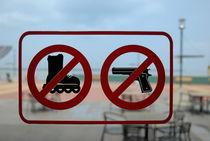 Restaurant entrance door with 'firearms' and 'roller-skates' forbidden sign von Sami Sarkis Photography