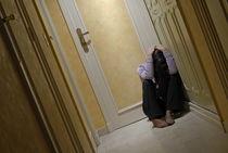 Depressed woman sitting in corridor with head in hands von Sami Sarkis Photography