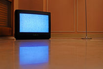 Television displaying static reflected in floor von Sami Sarkis Photography