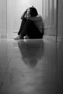 Woman sitting in corridor with head in hands by Sami Sarkis Photography