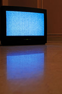Television displaying static reflected on floor by Sami Sarkis Photography