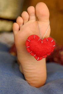 Valentine heart hanging on girl's barefeet by Sami Sarkis Photography