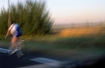Cyclist on road by Sami Sarkis Photography
