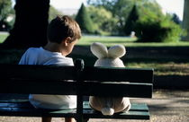 Boy (7-9) sitting on park bench with teddy bear by Sami Sarkis Photography