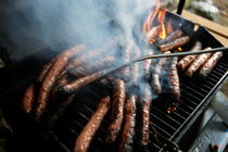 Sausages cooking on barbecue by Sami Sarkis Photography