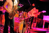 Woman playing saxophone on stage with her band by Sami Sarkis Photography